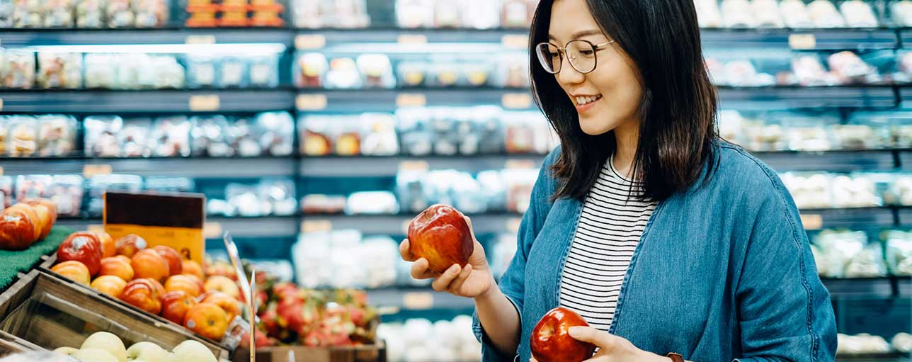 Woman picking apples in grocery store
